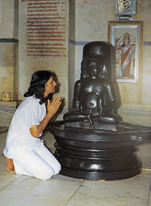 Ypung Amrit Desai kneels at Dadaji statue
